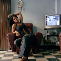 Woman posing in her living room, with Camillo Cienfuegos on the TV, October 2003